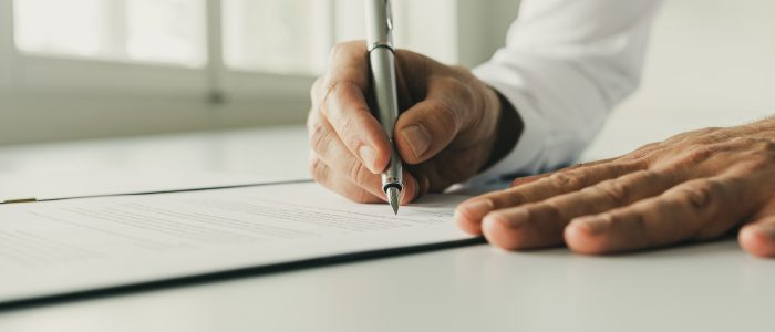 Wide low angle view image of businessman signing a document with silver ink pen.